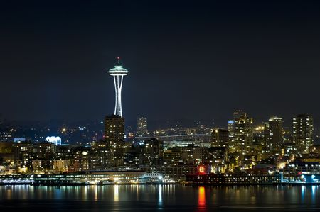 seattle: The iconic Seattle Skyline at night on an overcast night, as seen from West Seattle across the bay