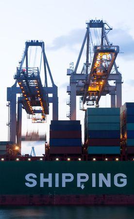 seafreight: La continua de carga con dos enormes gr�as de un mar va cargoship durante twillight hora.