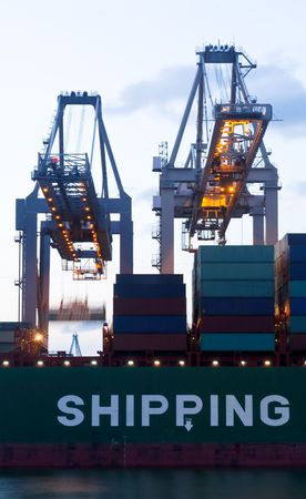seafreight: The continuous loading with two huge cranes of a sea going cargoship during twillight hour. Stock Photo