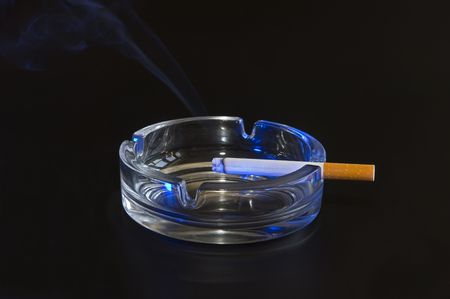 Burning cigarette in an ash tray against a black backdrop, lit by a blue strobe Stock Photo - 2079831