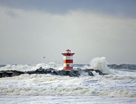 Waves crashing into the concrete pier leading to the lighthouse on a stormy day with gale force winds