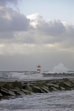 high winds: High winds and huge waves crashing into the harbor entrance during a fierce storm with gale force winds.