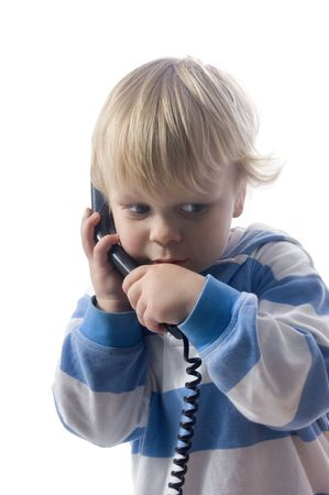 3 year old: A small, 3 year old boy whispering on the telephone
