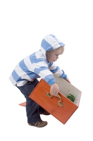 A three years old boy lifting a wooden toybox Stock Photo