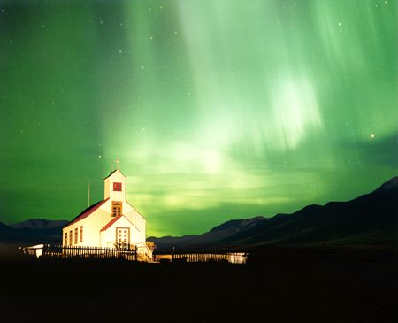 An illuminated church with the magnificent Aurora Borealis, or Northern Light lighting up the sky in Iceland photo