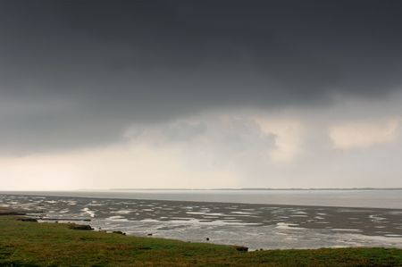zeeland: A thunderous sky over the Wester Schelde at low tide in Zeeland, the Netherlands Stock Photo