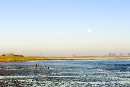 Salt flats and the sea dike shoreline with a full moon over the country photo
