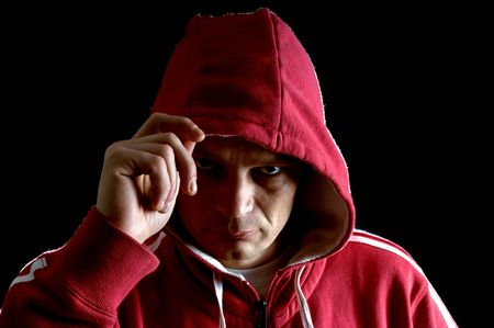 A grim looking hooligan, lifting his hood with his right arm, glaring at the camera. Stock Photo - 2367855