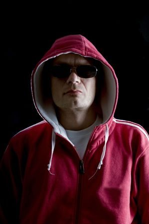 hoodlum: A grim looking Hoodlum wearing sunglasses, and looking mean Stock Photo