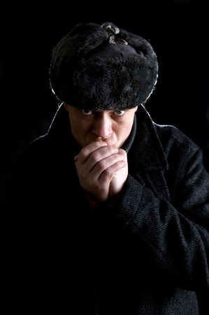 A man, dressed as a Russian, warming his hands photo