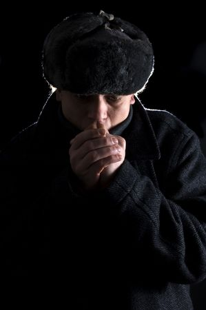 A man, dressed in Soviet attire, blowing in his cold hands Stock Photo - 2384195