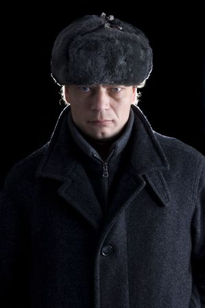 lapels: A stern looking man with a fur cap and a woolen coat looking straight into the camera Stock Photo