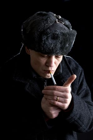 A man, dressed in Soviet attire, lighting a cigarette Stock Photo - 2384209