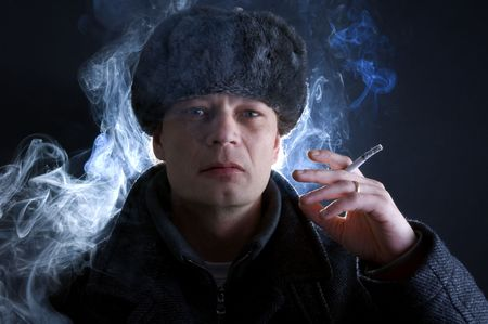 russian man: A man, dressed in Soviet attire, smoking a cigarette, surrounded by smoke.