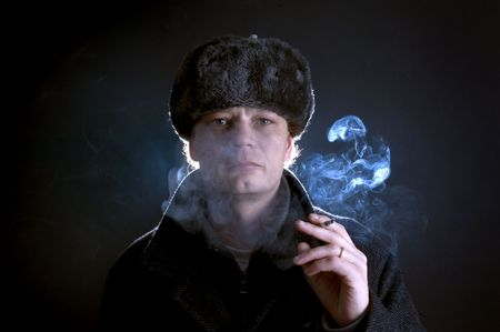 A man in his 30's, dressed as a former soviet, smoking a cigarette Stock Photo - 2384212