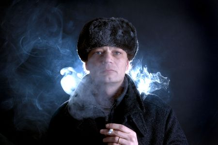 A man, dressed in Soviet attire, smoking a cigarette, surrounded by smoke photo