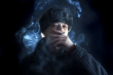 A man, dressed in a Soviet / Russian attire, smoking a cigarette Stock Photo - 2384198