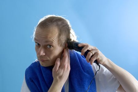 A middle aged man dressed in a white t-shirt, shaving his own hair with a clipper Stock Photo - 2488368