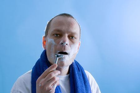 a middle aged man dressed in a white t-shirt, shaving himself Stock Photo - 2507397
