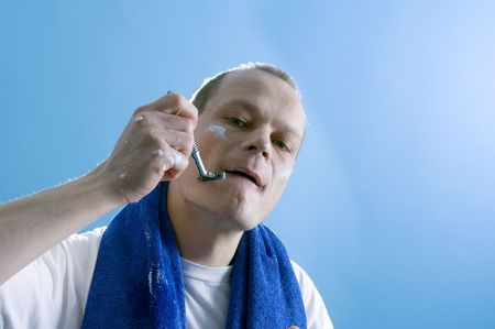 a middle aged man dressed in a white t-shirt, shaving himself Stock Photo - 2507400