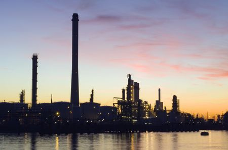 The silhouette of an oil refinery at sunset, against a radiant sky photo