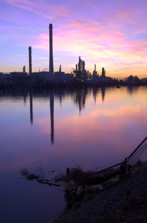 An oil refinery, situated in a commercial harbor, during a radiant sunset. HDR  image photo