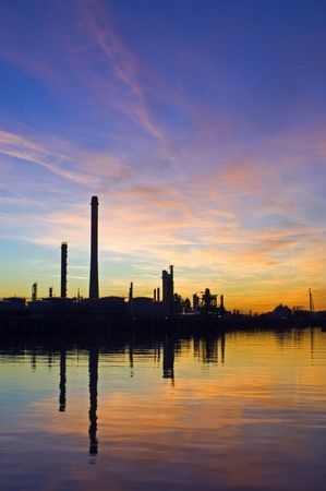 The silhouette of an oil refinery at sunset, against a radient sky photo