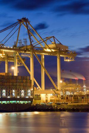 seafreight: El unloaing de un buque de carga generales de la utilizaci�n de grandes gr�as y carros, el transporte de contenedores hacia y desde el buque. Algunas chimeneas de humo en la distancia