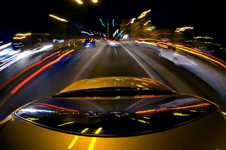 down lights: A car, surrounded by blurred other cars due to the high speed, driving in a busy down town area with lots of lights, traffic and traffic lights