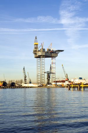 towed: An oil rig is being constructed in a harbor area, to be towed to sea after completion. Stock Photo