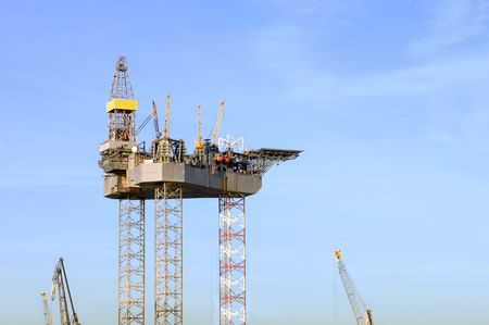 An oil rig is being constructed in a harbor area, to be towed to sea after completion. Stock Photo - 2613959