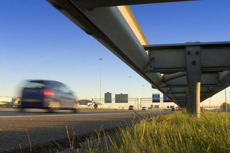 rail route: A motorway safety rail with route information sign and motion blurred passing cars