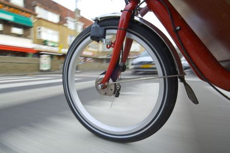 dynamo: The spinning and vibrating wheel of a delivery bicycle on a suburban street