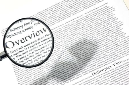 an overview: Keeping the overview amongst all finer details in life, using a magnifying glass on a piece of paper. Stock Photo