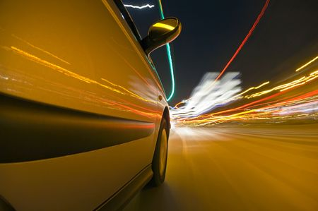bodywork: The side of a car, driving at high speed through urban streets, with the various lights passing by, reflecting in the bodywork