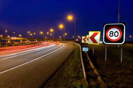 signos de precaucion: Las se�ales de advertencia en un cruce de autopistas por la noche