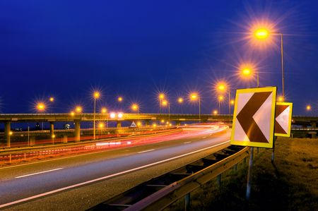 Cars soaring past on a motorway junction, their headlights lighting up the warning signs on the shoulder. Stock Photo - 2780045