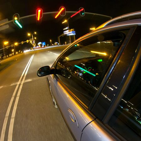 stopping: A car, reaching stand-still for the red lights of a traffic light at night