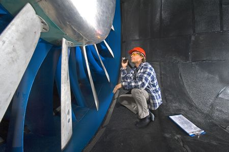 An engineer, wearing a checkered shirt, inspecting the rotors of a huge industrial windtunnel Stock Photo - 2953998