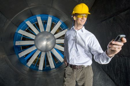 realms: A smiling engineer, looking at his phone inside the realms of an industrial windtunnel