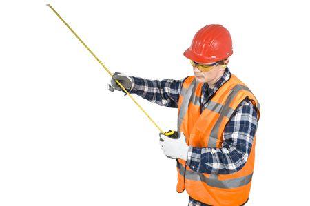 protection individuelle: Un travailleur de la construction, portait sa protection personnelle porter, en regardant une mesure sur un ruban � mesurer. Chemin de d�tourage inclus