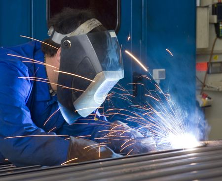 welding worker: A welder, wearing a protective helmet and fire retardant clothing, working on steel beams