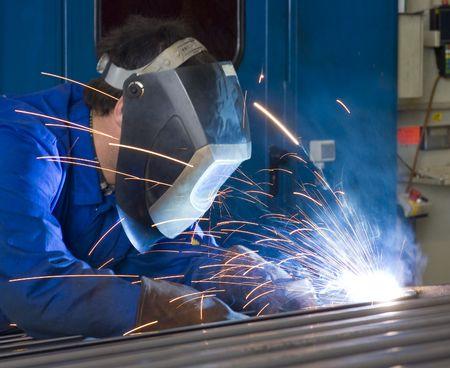 Ein Schweißer, trägt einen Schutzhelm und Flammschutzmittel Kleidung, arbeitet an Stahlträger