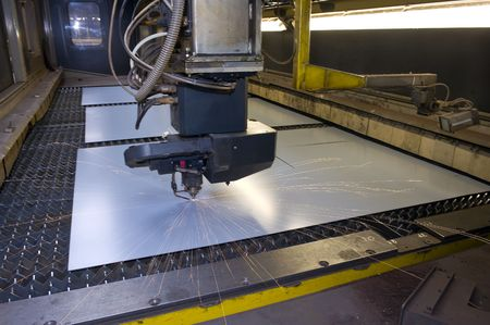 An industrial laser cutter, cutting through a steel sheet, with sparks flying everywhere photo