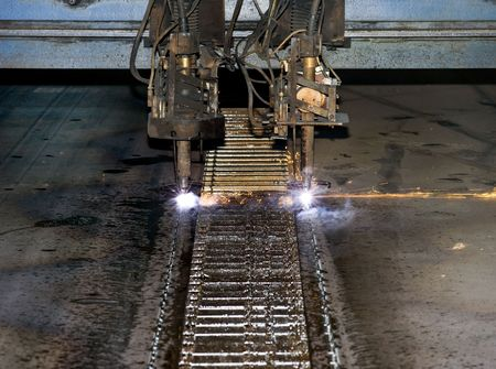 Detail of an industrial plasma cutter, cutting steel slabs into the desired width on a water cooled plasma cutting line photo