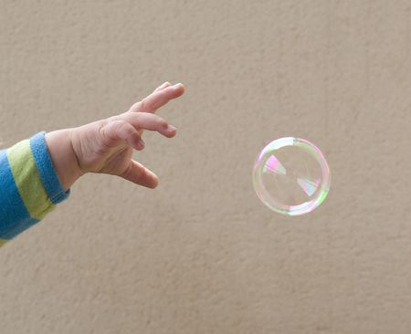 wanting: A babys hand, reaching for a soap bubble