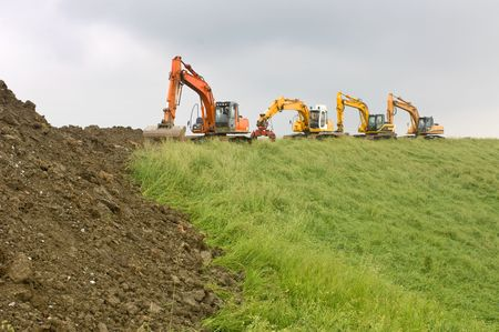 coast line: Four diggers on top of a dyke, at the works to reenforce the Dutch coast line on a grey, rainy day. Stock Photo