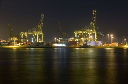 An overview of the Rotterdam Container harbor, with its huge cranes, stacked containers and industrial activity at night. Business continues 247 photo
