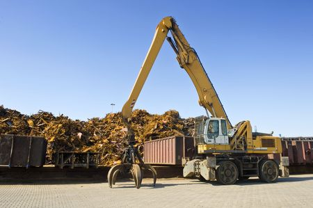 A crane with a huge claw in front of a steel scrap heap photo