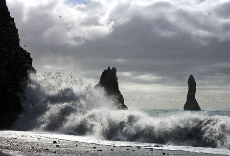 erecting: The waves of the Atlantic Ocean hitting the basalt and vulcanic beaches of Icelands south coast at Reynir, famous for its troll-like landmasses, erecting out from the ocean Stock Photo
